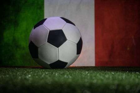 Traditional soccer ball on soccer field. Close up view of soccer ball (football) on green grass and flag of Italy on background. Selective focus