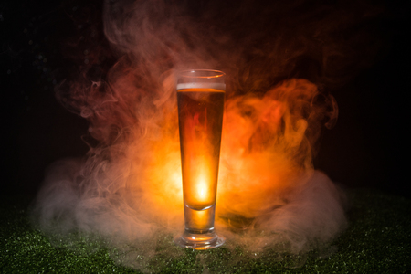 Creative concept. Single beer glass on green grass at dark toned foggy background. Watch football (soccer) with beer concept. Selective focus Stock Photo
