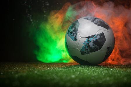BAKU,AZERBAIJAN - JUNE 21, 2018 : Creative concept. Official Russia 2018 World Cup football ball The Adidas Telstar 18 on green grass with dark toned foggy background. Selective focus