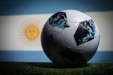 BAKU,AZERBAIJAN - JUNE 21, 2018 : Creative concept. Official Russia 2018 World Cup football ball The Adidas Telstar 18 on dark toned foggy background with flag of Argentina. Selective focus