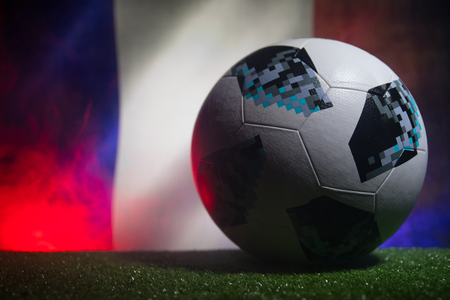 BAKU,AZERBAIJAN - JUNE 21, 2018 : Creative concept. Official Russia 2018 World Cup football ball The Adidas Telstar 18 on dark toned foggy background with flag of France. Selective focus
