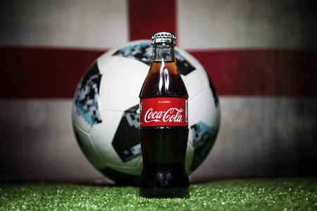 BAKU,AZERBAIJAN - JULY 01, 2018 : Creative concept. Official Russia 2018 World Cup football ball The Adidas Telstar 18 and Coca-Cola Classic in a glass bottle on grass. Support your country concept Editorial