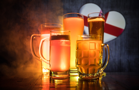 Soccer 2018. Beer glasses on table at dark toned foggy background. Support England with beer concept. Selective focus