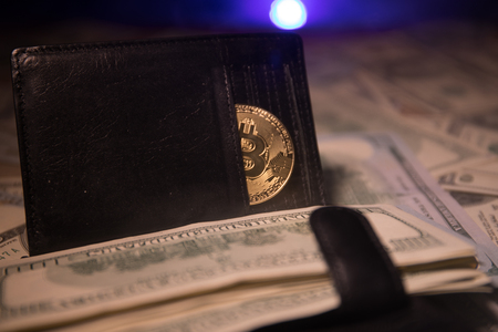 Bitcoin and a lot of dollars in leather wallet. Bitcoin with dollar in purse. Profit from mining crypto currencies. Miner with dollars and gold bitcoin. Bussiness, commercial. Selective focus