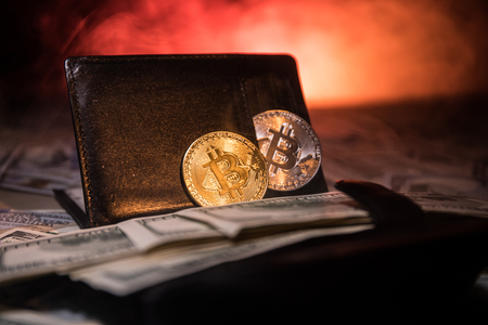 Golden and silver bitcoins and a lot of dollars in leather wallet. Bitcoin with dollar in purse. Profit from mining crypto currencies. Selective focus. Bussiness, commercial. Stock Photo