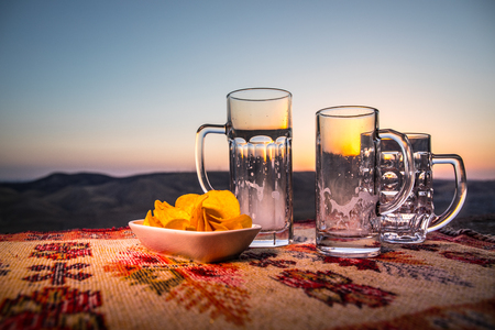 Close up empty mugs of beer on a sunrise background with mountains. Beer party is over concept. Selective focus Stock Photo