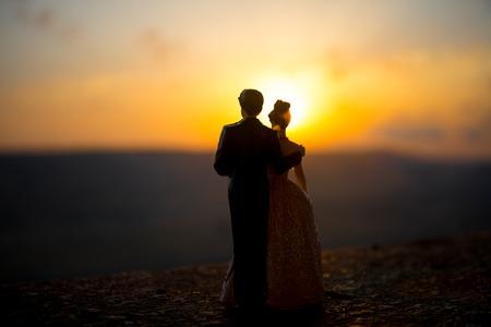 silhouet van bruiloft Paar standbeeld hand bij elkaar te houden tijdens zonsondergang met avondhemel achtergrond. Bruiloft concept. Selectieve aandacht Stockfoto