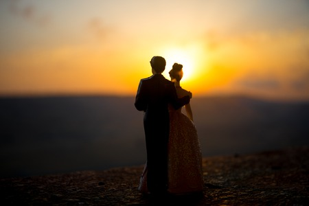 silhouette of wedding Couple statue holding hand together during sunset with evening sky background. Wedding concept. Selective focus