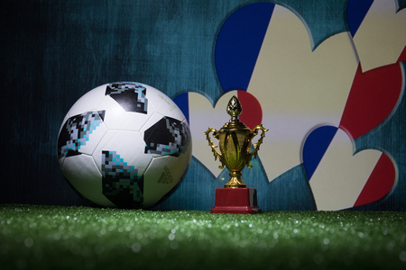 BAKU,AZERBAIJAN - JULY 13, 2018 : Creative concept. Official Russia 2018 World Cup football ball The Adidas Telstar 18 and Champion`s cup on green grass. Support France team concept. Selective focus