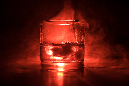 Glass of whiskey and ice on wooden surface with color light and fog on background. Close up. Advertising shot