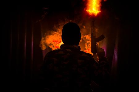 Silhouette d'homme avec fusil d'assaut prêt à attaquer sur fond brumeux aux tons sombres ou bandit dangereux en noir portant cagoule et tenant le pistolet à la main. Tir terroriste avec décor de thème d'arme