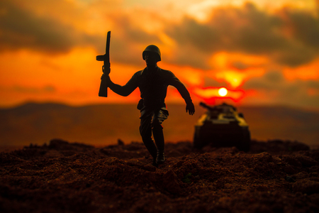 War Concept. Military silhouettes fighting scene on war fog sky background, World War Soldiers Silhouettes Below Cloudy Skyline at sunset. Soldier trying to escape from tank Imagens