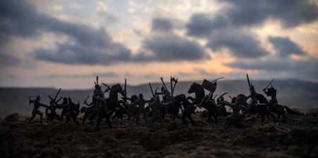 Średniowieczna scena bitwy z kawalerią i piechotą. Sylwetki postaci jako oddzielne obiekty, walka między wojownikami na mglistym tle zachodzącego słońca. Selektywna ostrość Zdjęcie Seryjne