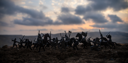 Medieval battle scene with cavalry and infantry. Silhouettes of figures as separate objects, fight between warriors on sunset foggy background. Selective focus Stok Fotoğraf