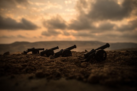 War Concept. Old artillery cannon guns on war fog sky background. Selective focus Imagens
