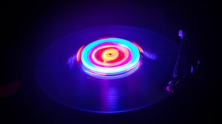 Concept de musique. Freezelight vinyle brillant sur fond sombre ou platine à jouer vinyle avec des lignes abstraites rougeoyantes concept sur fond sombre. Pour la conception d'affiche de club