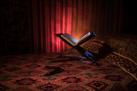 Open holy book of Muslims on stand on eastern carpet with dark toned foggy background. Muslim religion concept. Selective focus. Indoor shot.