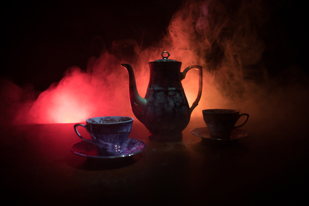 Coffee or tea ceremony conceptual theme. Old vintage ceramic tea or coffee pot with cups on dark toned background with light and smoke. Empty space for text. Selective focus