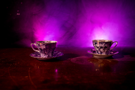 Coffee or tea ceremony conceptual theme. Old vintage ceramic tea or coffee cups on dark toned background with light and smoke. Empty space for text. Selective focus Stock Photo