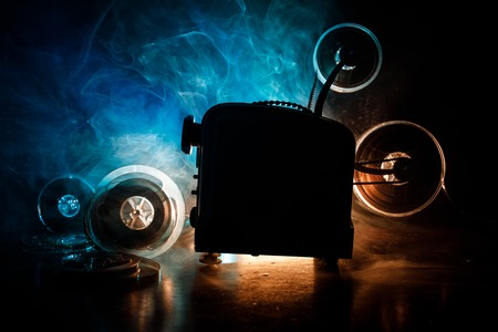 Old style movie projector, still-life, close-up. Film projector on a wooden background with dramatic lighting and selective focus. Movies and entertainment concept Stock Photo