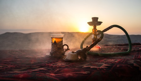 Hookah hot coals on shisha bowl making clouds of steam at desert outdoor. Oriental ornament on the carpet eastern tea ceremony. Stylish oriental shisha on sunset background. Selective focus