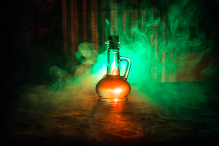 Antique and vintage glass bottle on dark foggy background with light. Poison or magic liquid concept. Stock Photo