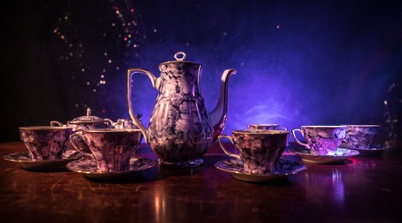 Coffee or tea ceremony conceptual theme. Old vintage ceramic tea or coffee pot with cups jug and sugar cup on dark toned background with light and smoke. Empty space for text. Selective focus