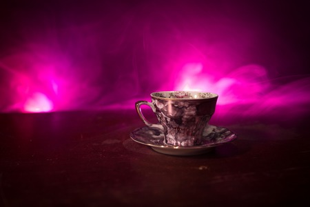Coffee or tea ceremony conceptual theme. Old vintage ceramic tea or coffee cup on dark toned background with light and smoke. Empty space for text. Selective focus Stock Photo
