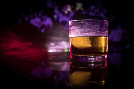 Selective focus pure whisky with ice cube inside whisky glass on dark foggy background alcohol drink concept. Close up