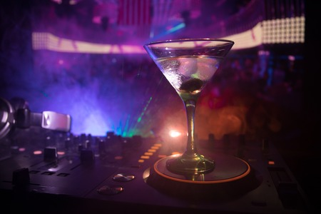 Glass with martini with olive inside on dj controller in night club. Dj Console with club drink at music party in nightclub with disco lights. Stock Photo