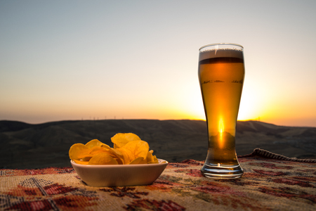 Close Up of A Glass of Beer with the snacks on Sunlight Background. Selective focus