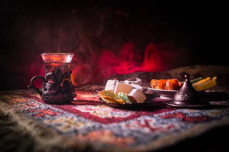 Arabian tea in glass with eastern snacks on a carpet on dark background with lights and smoke. Eastern tea concept. Empty space. Selective focus.
