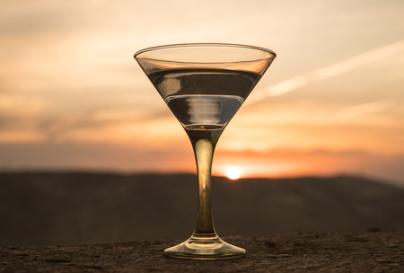 Martini in a glass against sunset background with mountains. Club drink at sunset time. Selective focus