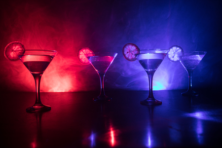 Several glasses of famous cocktail Martini, shot at a bar with dark toned foggy background and disco lights. Club drink concept. Selective focus
