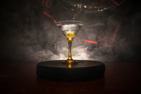 glass with martini with olive inside. Close up view of glass with club drink on dark foggy toned background. Selective focus. Club drink concept Stock Photo