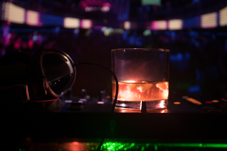 Glass with whisky with ice cube inside on dj controller at nightclub. Dj Console with club drink at music party in nightclub with disco lights. Selective focus