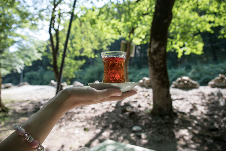 Eastern black tea in glass on woman`s hand at forest. Eastern tea concept. Armudu traditional cup. Green nature background. Selective focus