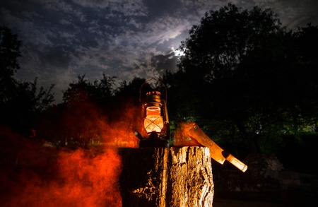 Horror Halloween concept. Burning old oil lamp in forest at night. Night scenery of a nightmare scene. Selective focus. Stock Photo