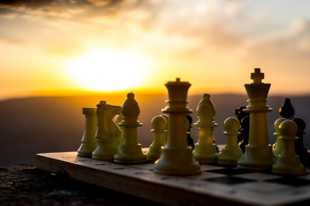 chess board game concept of business ideas and competition and strategy ideas. Chess figures on a chessboard outdoor sunset background. Selective focus