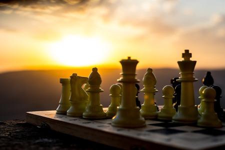 schaakbordspelconcept van zakelijke ideeën en concurrentie- en strategie-ideeën. Schaken cijfers op een schaakbord buiten zonsondergang achtergrond. Selectieve focus