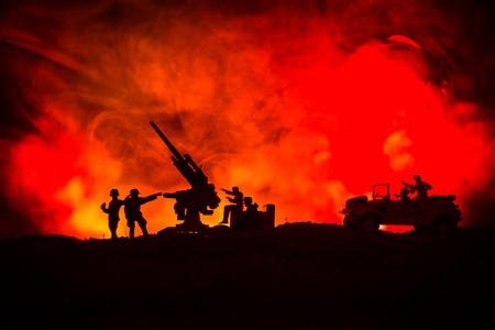 Un cañón antiaéreo y siluetas militares luchando contra la escena en el fondo del cielo de niebla de guerra, siluetas de soldados de la guerra mundial debajo del horizonte nublado en la noche Foto de archivo