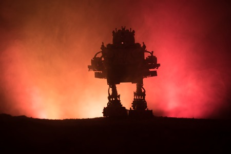 Silhouette of Giant robot. Futuristic tank in action with foggy fire sky background. Combat vehicle. Archivio Fotografico - 110202991