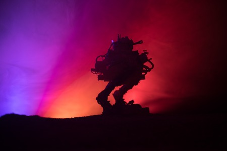 Silhouette of Giant robot. Futuristic tank in action with foggy fire sky background. Combat vehicle.