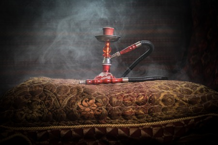 Hookah hot coals on shisha bowl making clouds of steam at Arabian interior. Oriental ornament on the carpet. Stylish oriental shisha with backlight. For Shisha advertisement. Selective focus