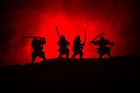 Silhouette of samurais with swords. Picture with four samurais and sunset sky. Selective focus Reklamní fotografie