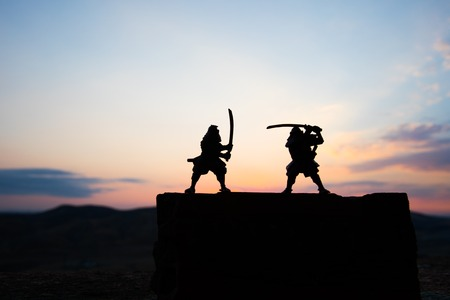 Silhouette of two samurais in duel. Picture with two samurais and sunset sky. Selective focus Reklamní fotografie