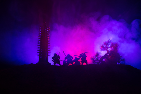 Samurai fighting concept. Silhouette of samurais in duel near tree and old temple. Table decoration with dark toned foggy background. Selective focus Stock Photo