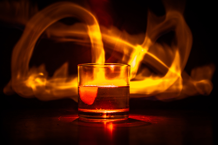 Whiskey in fire concept. Glass of whiskey and ice on wooden surface with color light and fog on background. Close up. Selective focus Stock Photo