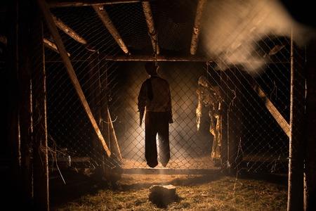 夜の足場に絞首刑の男のホラービューシルエットは、霧と背景に引き締まった光を持っています。