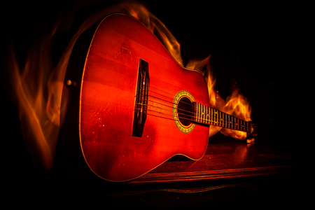 Music concept. Acoustic guitar on a dark background under beam of light with smoke